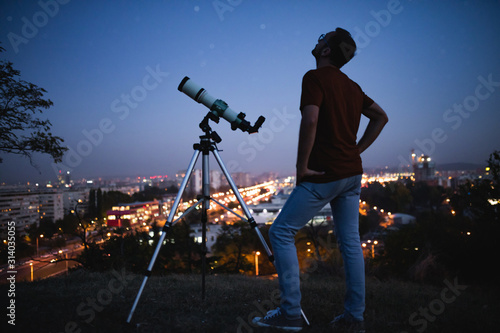 Fototapeta Astronomer with a telescope watching at the stars and Moon with blurred city lights in the background. obraz