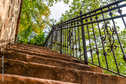 Cuadros en Lienzo Close up of staircase with stone treads and metal railing against leaves and sky