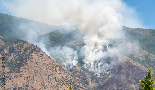 Nature landscape with puffs of white smoke rising from mountain forest fire
