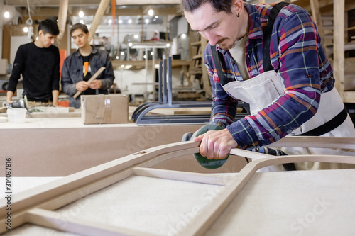 Young serious man hipster master carpenter in shirt on wood industry makes a new product for the next collection Wallpaper Mural