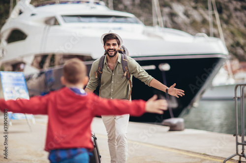 Obraz Happy father hugging little son arriving returning after long trip - fototapety do salonu