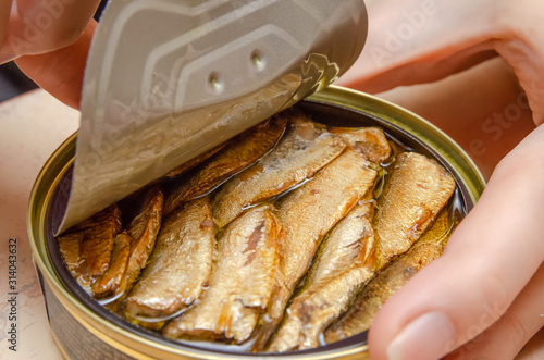 Photo Female hands open a can of fish sprats on the table close up