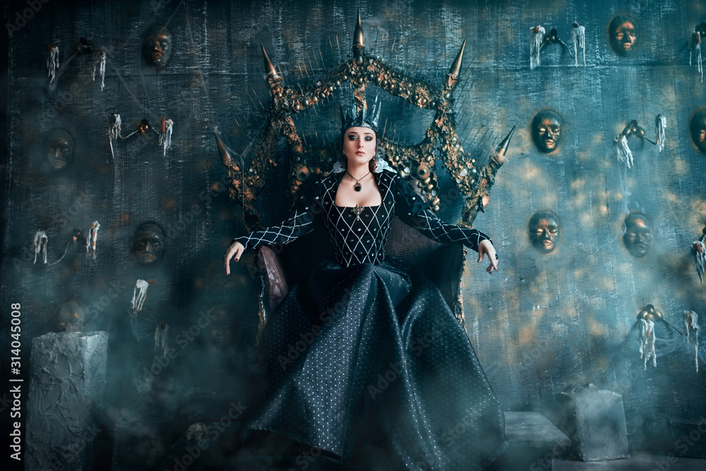Fototapeta Evil Queen in a black dress. Beautiful girl in the crown sits on the throne