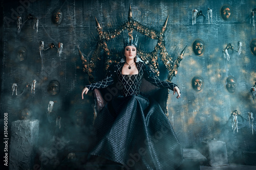 Obraz Evil Queen in a black dress. Beautiful girl in the crown sits on the throne - fototapety do salonu