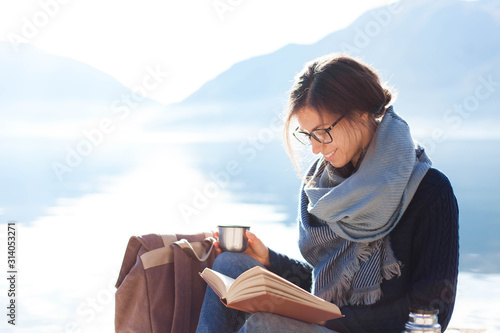 Young woman reading book at sea beach. Cozy winter picnic by morning mountains. Happy student in blue scarf enjoying traveling. Girl traveler drinks coffee. Solo female tourism. Lifestyle moment.