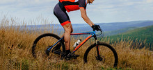 Male Cyclist Downhill Rides Trail In Dry Grass. Mud On Feet And Mountain Bike