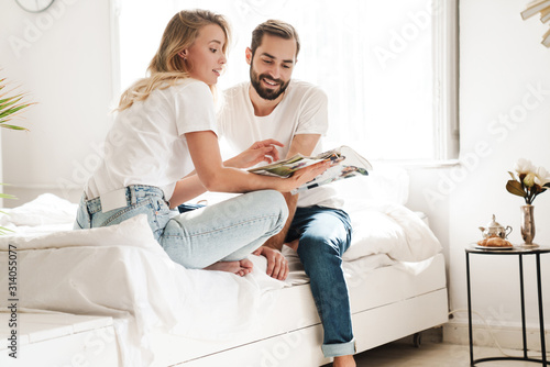 Obraz Happy young couple in love relaxing on a couch - fototapety do salonu