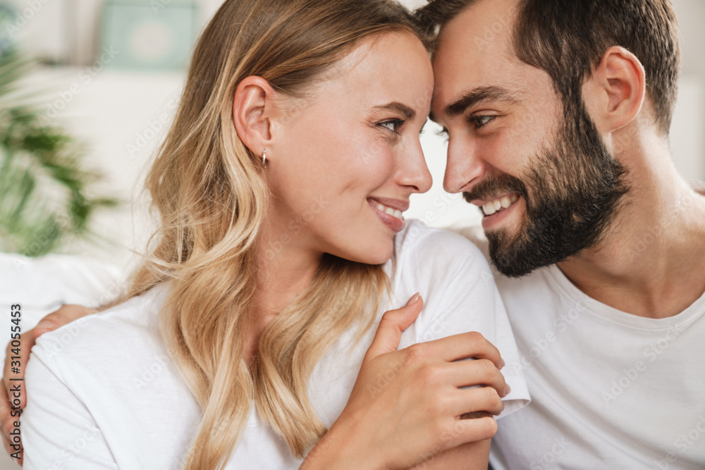 Fototapeta Beautiful happy young couple in love embracing at home