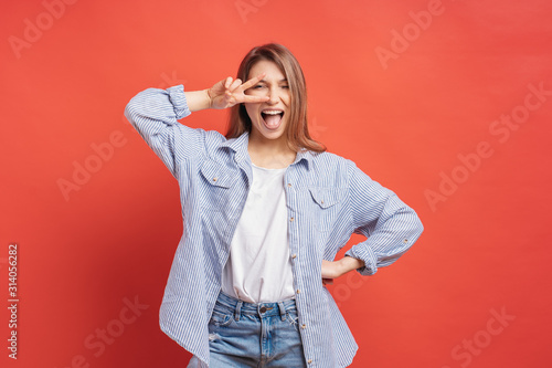 Funny, carefree girl having fun isolated on a red background with open mouth