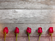 Five Red Roses On The Old Table