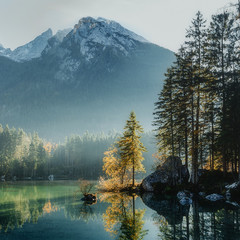 Fototapeta Rzeki i Jeziora Wonderful Autumn. Sunny Misty Morning at Hintersee Lake in Bavaria, Germany. Amazing sunset on the mountain lake. wonderlust view of nature with autumn trees under sunlight. amazing nature background