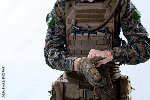 closeup of soldier hands putting protective battle gloves Fototapeta