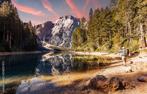 Wall mural - Wonderful sunrise view of Braies lake. Dramatic Unusual Scene. Colorful Sky over lago di Braies in Dolomites Alps. Awesome Alpine Highlands during sunset. Amazing nature Landscape at Summer Day.