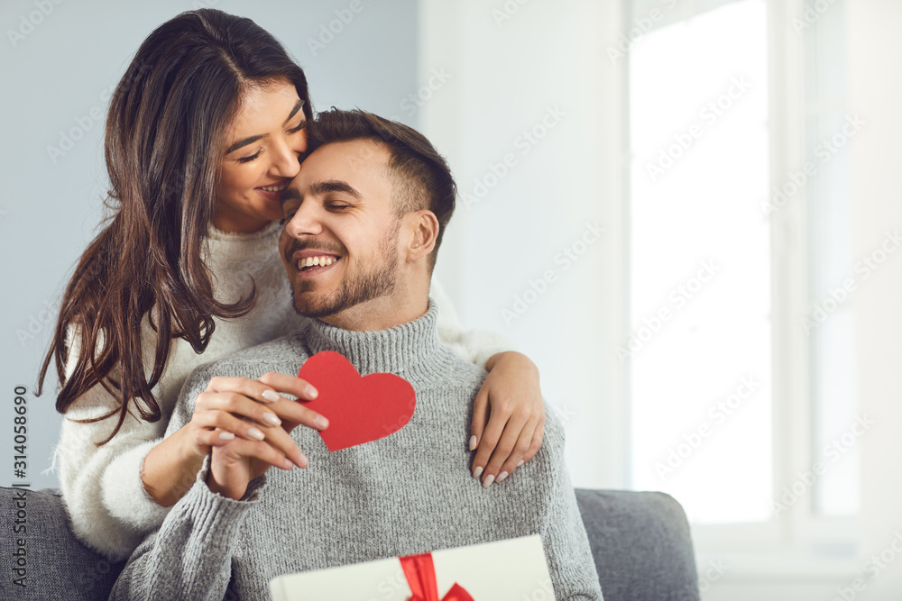 Fototapeta Valentine's day. Couple gives heart to the Valentine's Day in the room.