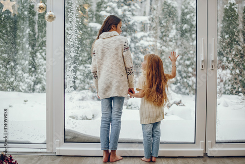 Fototapeta Cute childrens at home. Kids in a Christmas decorations. Sisters in a cute sweaters. obraz