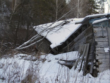 Old Ruined Wooden House In The Forest. Abandoned Building In The Mountains In Winter. Decrepit Dilapidated House. Rustic Grunge Background. A Collapsed Shack In The Snow.