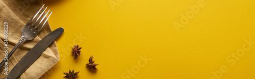 Fototapeta top view of anise near cutlery on beige napkin on yellow background, panoramic shot obraz