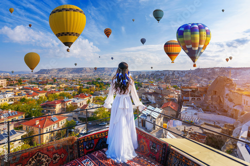 Obraz Beautiful girl standing on the hotel and looking to hot air balloons in Cappadocia, Turkey. - fototapety do salonu