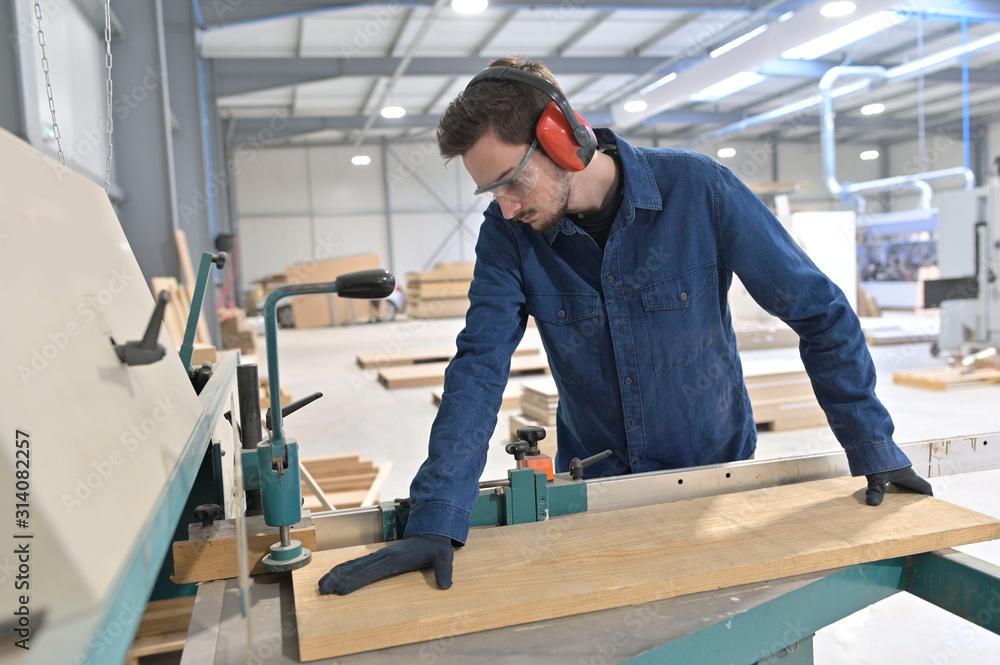 Fototapeta Apprentice working wood in carpentry workshop