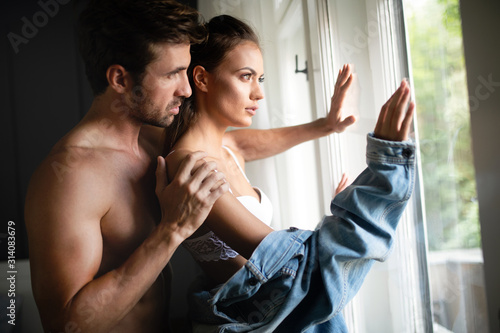 Obraz na plátně Beautiful woman and handsome muscular man close to each other in erotic pose