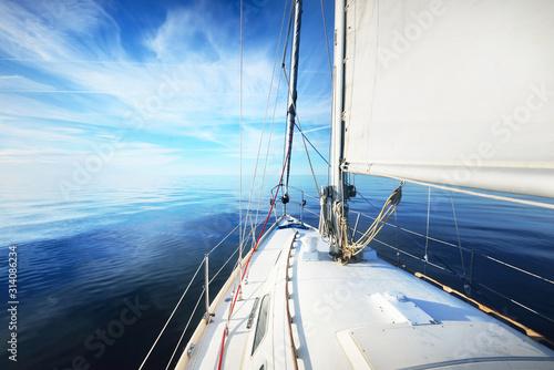 Biały jacht takielunek slupowy żegluje na otwartym morzu bałtyckim w pogodny, słoneczny dzień. Widok z pokładu na dziób. Estonia