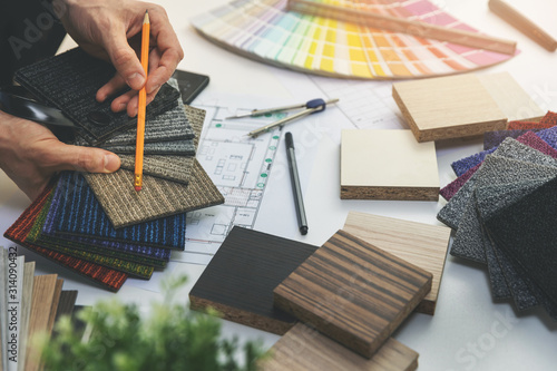 Fototapeta designer choosing flooring and furniture materials from samples for home interior design project obraz