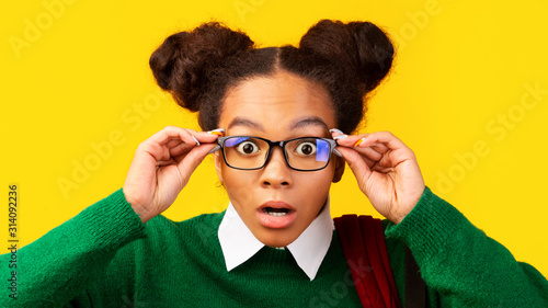 Vászonkép  Amazed afro teenager with opened mouth touching glasses