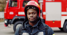 Portrait Of African American Brave Fireman Standing Near Fire Truck