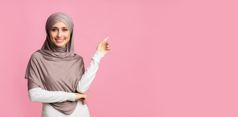 Smiling arabian girl pointing at copy space over pink background