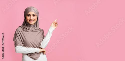 Fototapeta Smiling arabian girl pointing at copy space over pink background obraz