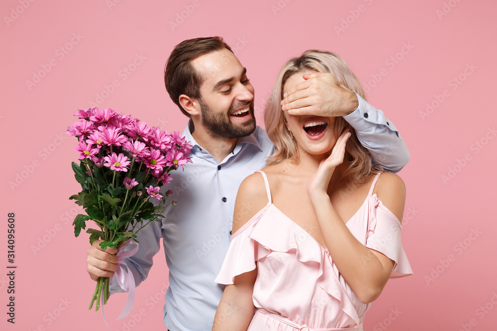 Fototapeta Cheerful young couple two guy girl in party outfit celebrating isolated on pastel pink background. Valentine's Day Women's Day birthday holiday concept. Hold bouquet of flowers, cover eyes with hand.