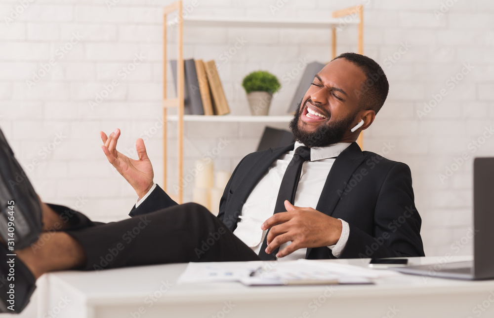 Fototapeta Emotional afro businessman listening to music at workplace