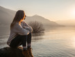 canvas print picture - Young woman witting on rock by the lake at sunset looking at view and enjoying the serene atmosphere. Girl relaxing in winter contemplating nature