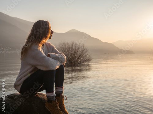 Fotografie, Obraz Young woman witting on rock by the lake at sunset looking at view and enjoying the serene atmosphere