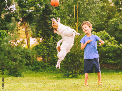 Leinwand Poster Happy kid looking at jumping dog catching basketball ball