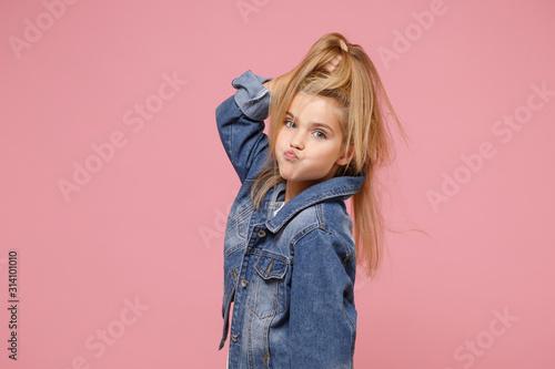Fototapeta Pretty little blonde kid girl 12-13 years old in denim jacket isolated on pastel pink background children studio portrait