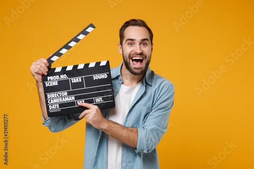 Fototapeta Excited young man in casual blue shirt posing isolated on yellow orange wall background, studio portrait