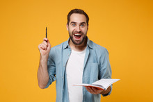 Excited Young Student Man In Casual Blue Shirt Posing Isolated On Yellow Orange Background In Studio. People Sincere Emotions Lifestyle Concept. Mock Up Copy Space. Holding Notebook, Pointing Pen Up.