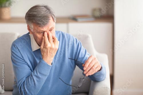 Cuadros en Lienzo Senior Man Massaging Nosebridge Sitting On Sofa, Selective Focus