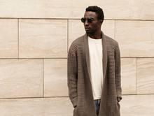 Stylish African Man Model Looking Away Wearing Brown Knitted Cardigan, Sunglasses On City Street Over Brick Wall Background