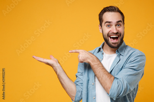 Fototapeta Excited young bearded man in casual blue shirt posing isolated on yellow orange background, studio portrait. People emotions lifestyle concept. Mock up copy space. Pointing index finger, hand aside. obraz