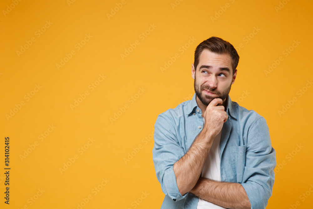 Fototapeta Pensive young bearded man in casual blue shirt posing isolated on yellow orange background studio portrait. People emotions lifestyle concept. Mock up copy space. Put hand prop up on chin, looking up.
