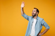 Cheerful young bearded man in casual blue shirt posing isolated on yellow orange background in studio. People lifestyle concept. Mock up copy space. Waving and greeting with hand as notices someone.