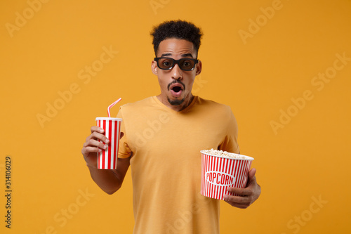 Photo  Shocked young african american guy in 3d imax glasses posing isolated on yellow orange background