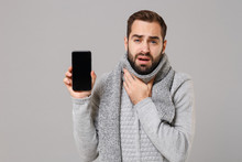 Man In Gray Sweater, Scarf Isolated On Grey Background. Healthy Lifestyle, Ill Sick Disease Treatment, Cold Season Concept. Mock Up Copy Space. Hold Mobile Phone With Blank Screen, Put Hand On Throat.