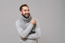 Laughing Young Man In Gray Sweater, Scarf Posing Isolated On Grey Wall Background, Studio Portrait. Healthy Fashion Lifestyle, Cold Season Concept. Mock Up Copy Space. Pointing Index Finger Up Aside.