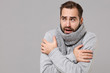 Frozen young man in gray sweater posing isolated on grey wall background, studio portrait. Healthy fashion lifestyle, cold season concept. Mock up copy space. Holding hands folded, huging himself.