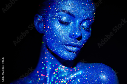 Fotografie, Obraz Fashion model woman in blue bright sparkles and neon lights posing in studio