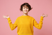 Funny Young Brunette Woman Girl In Yellow Sweater Posing Isolated On Pastel Pink Background. People Lifestyle Concept. Mock Up Copy Space. Hold Hands In Yoga Gesture Relaxing Meditating Looking Aside.