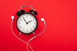 Leinwanddruck Bild - minimalism concept. alarm clock with headphones on a red background with copy space